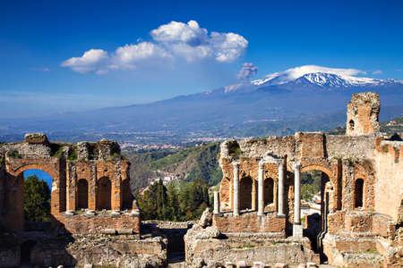 Le rovine del Teatro Greco Romano con l'Etna in eruzione, Taormina, Sicilia, Italia