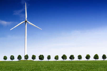 Wind Turbine on front of a green wheat field and line of trees photo