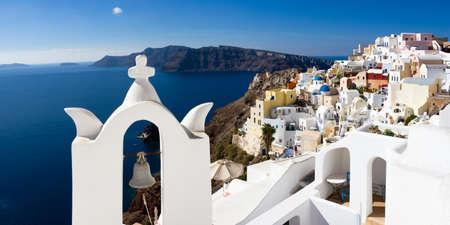 cycladic: Bianco campanile sopra il Mar Mediterraneo con il villaggio delle Cicladi Oia sullo sfondo, Santorini, Grecia