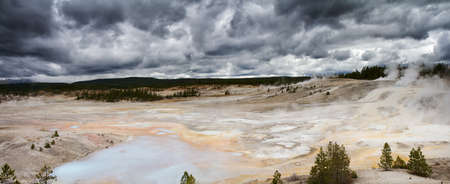 volcanism: Panorama of Norris Geyer Basin under dark clouds, Yellowstone National Park, Wyoming
