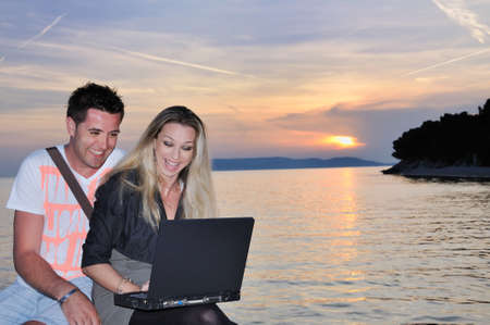 Couple of students working on computer on sunset photo