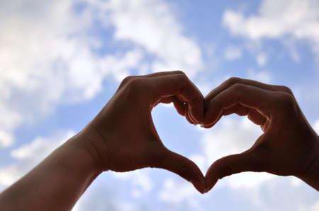 corazon en la mano: Manos en forma de amor en el cielo azul