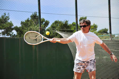 Middle age man playing tennis photo