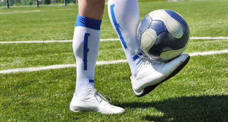 Human leg and soccer ball on the grass field photo
