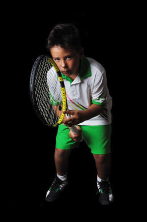 Tennis boy isolated in black photo