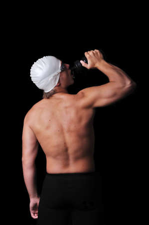 Male swimmer drinking water isolated in black photo