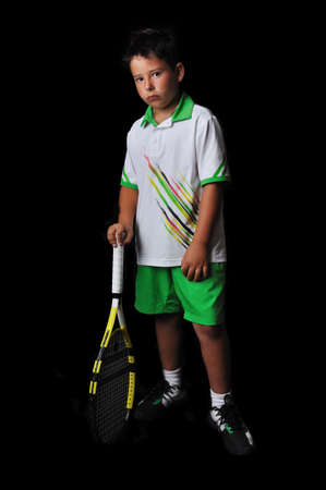 Tennis boy posing isolated in black photo