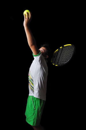 Tennis boy serving isolated in black