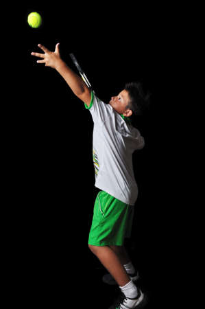 tennis serve: Tennis boy serving isolated in black