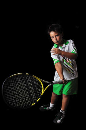 Tennis boy playing forehand isolated in black photo