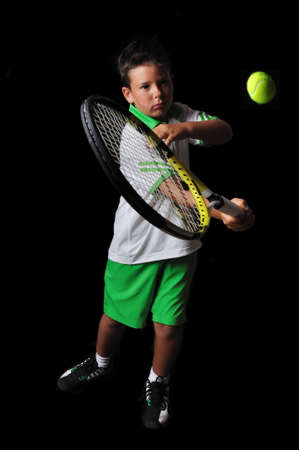 forehand: Tennis boy playing forehand isolated in black