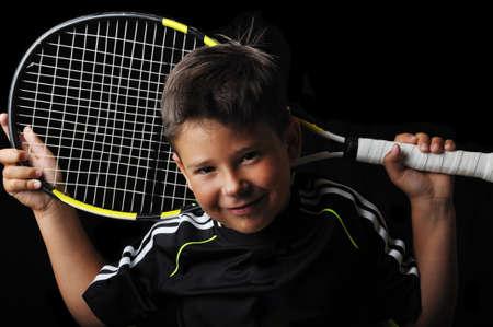 jugando tenis: Chico de tenis sonriente aislado en negro