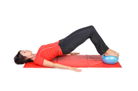 Fit young female pilates instructor showing different exercises with ball on a white background Stock Photo - 12781029