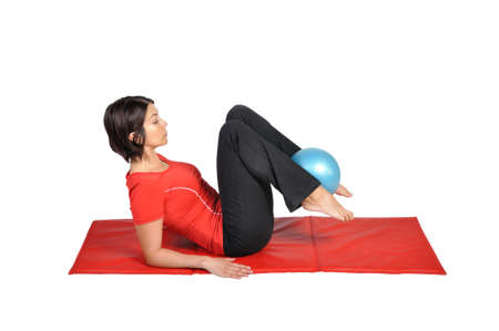 toning: Fit young female pilates instructor showing different exercises with ball on a white background  Stock Photo