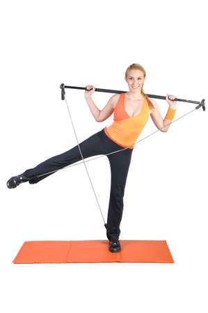 Fit young female pilates instructor showing different exercises on a white background photo