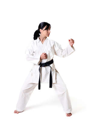girl kick: Karate woman posing on a white background