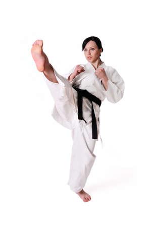 patada: Karate mujer posando sobre un fondo blanco Foto de archivo