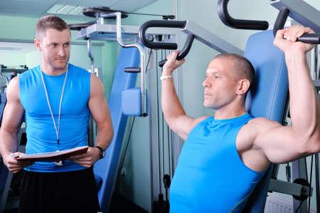 aide à la personne: Homme sportif dans le gymnase avec entraîneur personnel