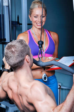 Athlete man in gym with personal fitness trainer photo