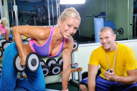 Woman in gym exercising with personal fitness trainer photo
