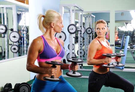 Dos mujeres hermosas que ejercitan en el gimnasio con pesas