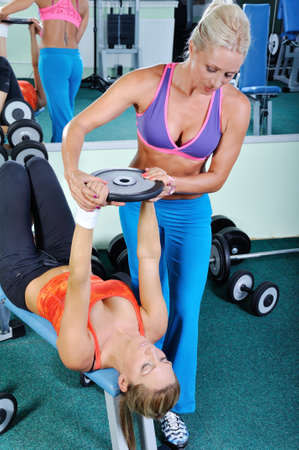 aide à la personne: Deux belles femmes exerçant dans le gymnase avec des poids