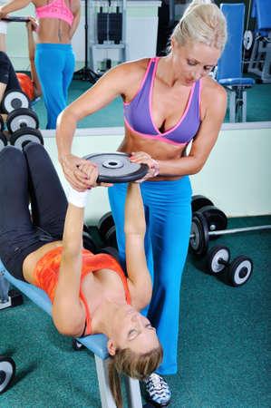 levantar peso: Dos mujeres hermosas que ejercitan en el gimnasio con pesas