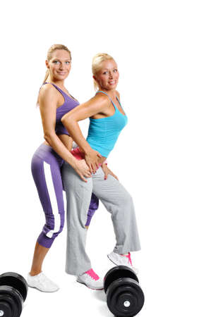 Two muscle women posing on a white background with dumbbells photo