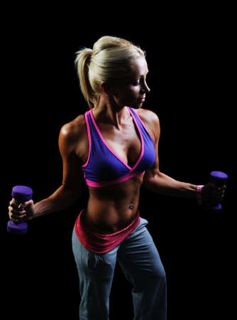 body building: Beautiful muscular woman exercise on a black background