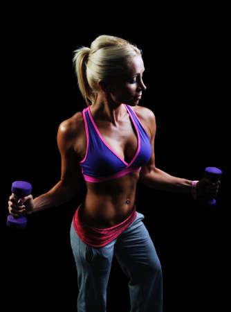 Bella donna esercizio muscolare su sfondo nero