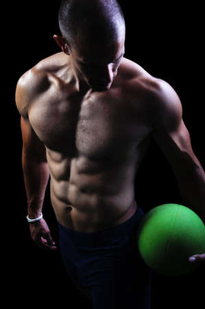 musculoso: Atleta muscular ejercicio del hombre sobre un fondo negro