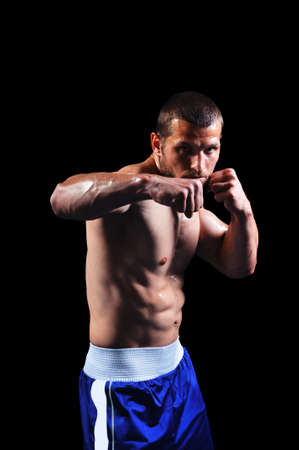 fighter: Powerful muscular boxer posing on black background