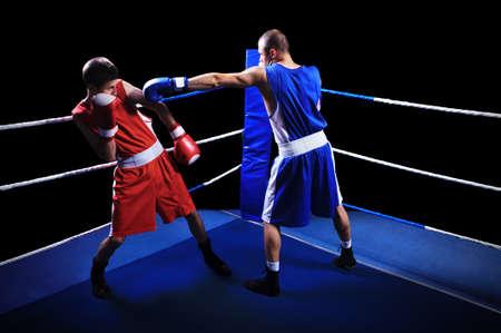 boxeadora: Dos boxeadores masculinos luchando en anillo