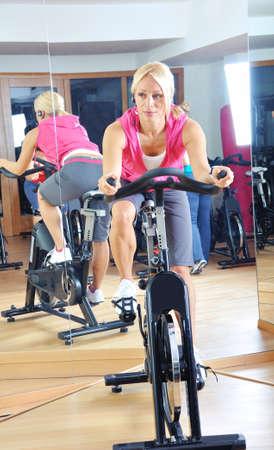 Belle femme faisant l'exercice dans une classe de spinning au gymnase