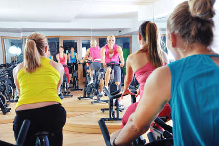 class room: Beautiful women doing exercise in a spinning class at gym