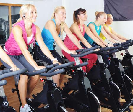 haciendo ejercicio: Hermosas mujeres haciendo ejercicio en una clase de spinning en el gimnasio Foto de archivo