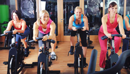 spinning wheel: Beautiful women doing exercise in a spinning class at gym