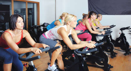 wheel spin: Beautiful women doing exercise in a spinning class at gym