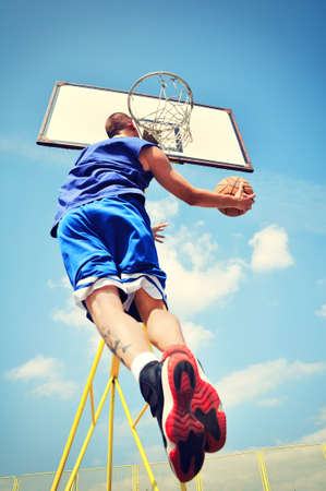 Basketball player in action flying high and scoring photo