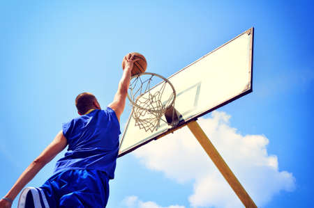 basketball player: Basketball player in action flying high and scoring Stock Photo