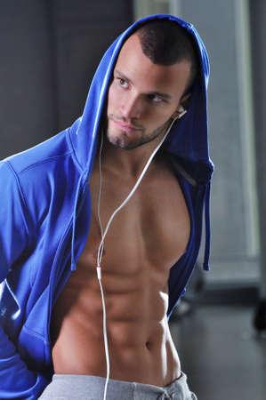 atletismo: Handsome Muscular modelo masculino con capucha T Shirt and Perfect Body Posando Foto de archivo