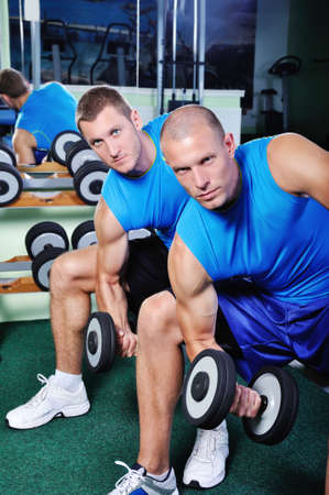 Muscular man exercising in a gym photo