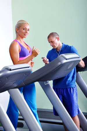 Beautiful women exercising in gym with personal fitness trainer photo