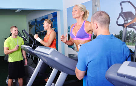 Two women in gym exercising with personal fitness trainer photo