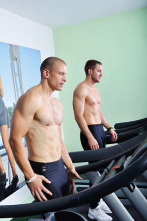 Two handsome men in gym running on the ergometer photo