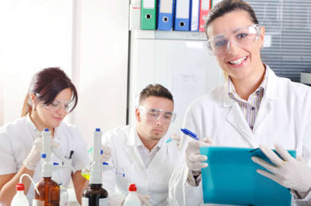 pharmacy technician: Attractive young PhD student scientist with two colleague out of focus behind her in chemical laboratory