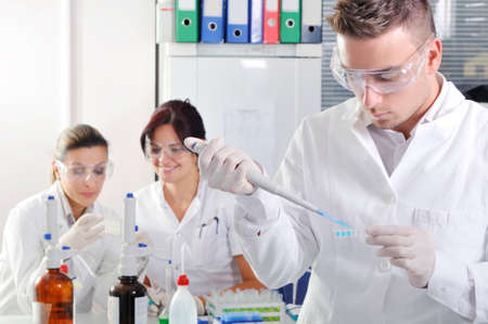 lab coats: Attractive young PhD student scientist with two colleague out of focus behind him in chemical laboratory Stock Photo