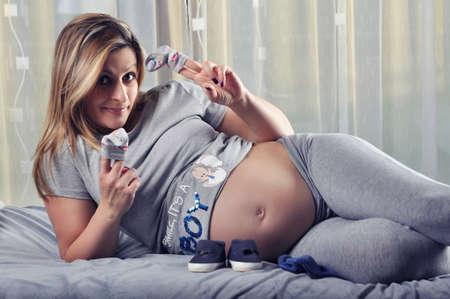 unborn: Happy future mommy showing her unborn baby boy socks