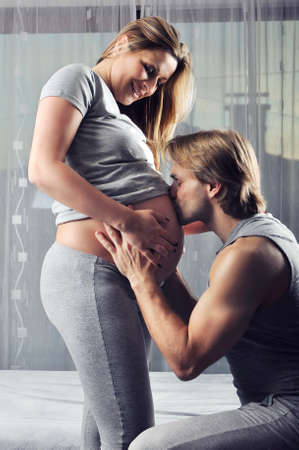 unborn: Happy future daddy kissing his unborn baby boy Stock Photo