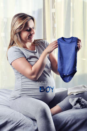 unborn: Happy future mommy smiling and showing unborn baby boy suit
